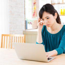 ノートパソコンの前で悩んでいる女性